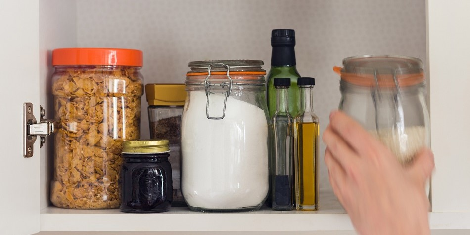 Hand reaching into cupboard to grab mason jar full of sugar